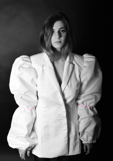 This look was inspired by rape culture and how women are viewed in modern society.  The look combines elements of tradional young, feminine clothing and sexy, almost lingerie pieces.  The purity of the white jacket with puff sleeves and baby pink ribbon details juxtaposes the black mesh and leather of the garter belt and cropped stockings. It is commentary on how women are punished for being too innocent and too sexy at the same time by the patriarchal standards society has set.