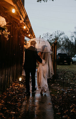 A bride and groom walking in the rain during their Louisiana wedding