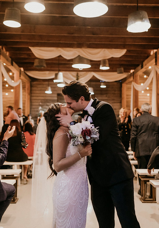 A bride and groom kiss at the end of the aisle after saying I do on their wedding day in Louisiana.