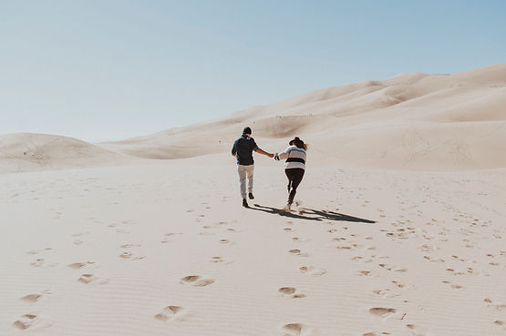 A couple run hand in hand through the Great Sand Dunes in Colorado