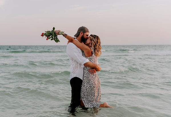 A couple kissing on the beach during a photoshoot