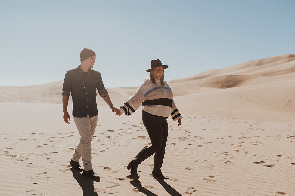 A couple walks through the Great Sand Dunes in Colorado