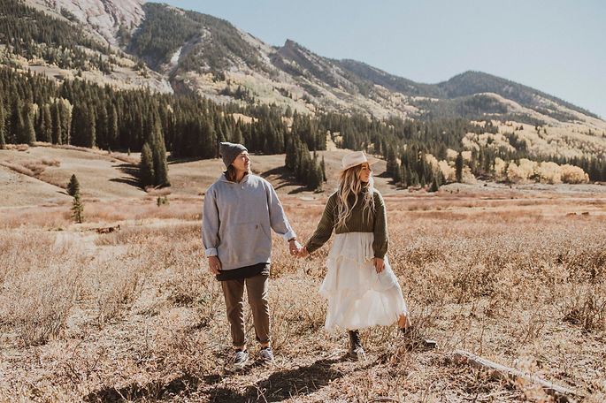 a couple stand hand in hand in the mountains in Crested Butte, Colorado.