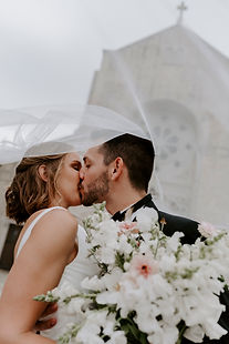 a bride and groom kiss in front of the church after getting married in Baton Rouge, Louisiana.