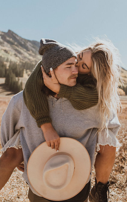 A couple does a piggy back ride in the mountains during their photoshoot