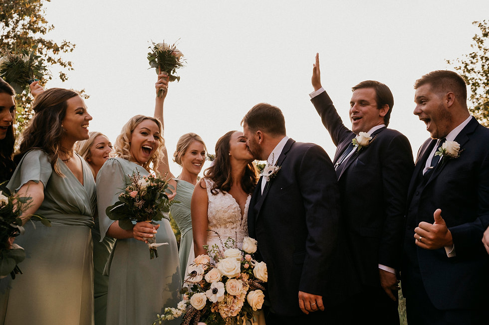 Bride and Groom kissing while bridal party celebrates