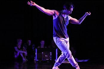 Dancer Alexander Davis onstage wearing a dark tank top and light pants.