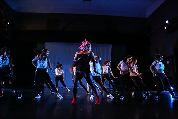 Chris Suharlim in a black corset and gloves, with 8 dancers behind. All are mid-hair-flip.