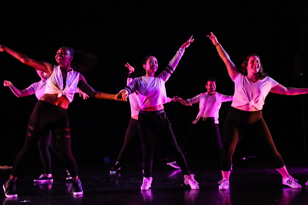 Group of dancers wearing black & white, perform under pink stage light.