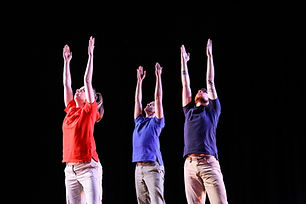 3 April Sellers' dancers, in red and blue polo shirts, reach straight overhead.