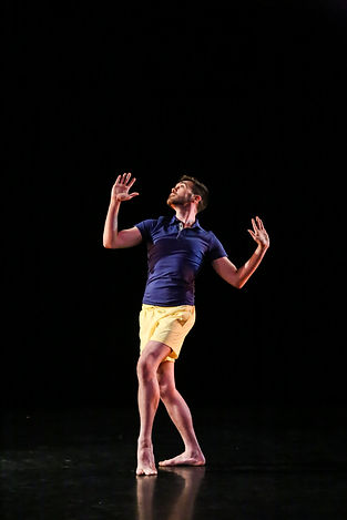 Michael on stage in a blue shirt and yellow shorts. He looks up, hands flexed and leaning upstage.