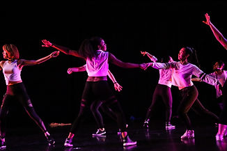Dancers in white tops, dark pants, and sneakers move across the stage, reaching toward each other.