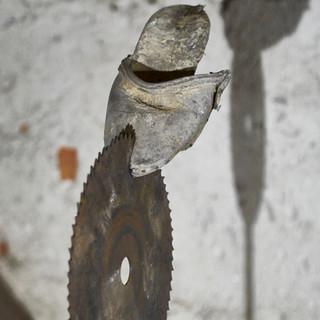 aus der serie 'bestandsaufnahme', o.t., 2021, stein, eisen, sägeblatt, holzschuh, 105 x 38 x 29 cm
