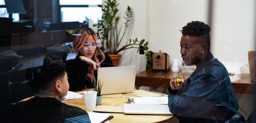 A group of co-workers of varying genders having a meeting.jpg