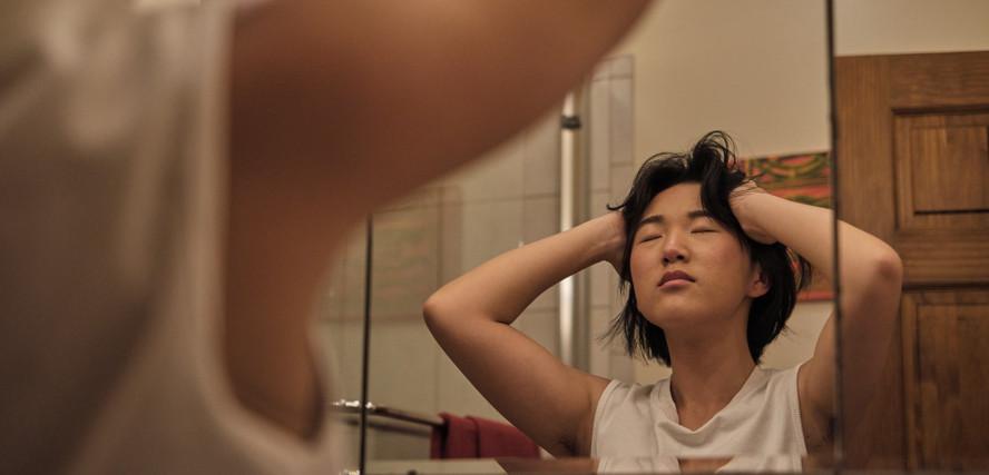 A non-binary trans man massaging his head.jpg