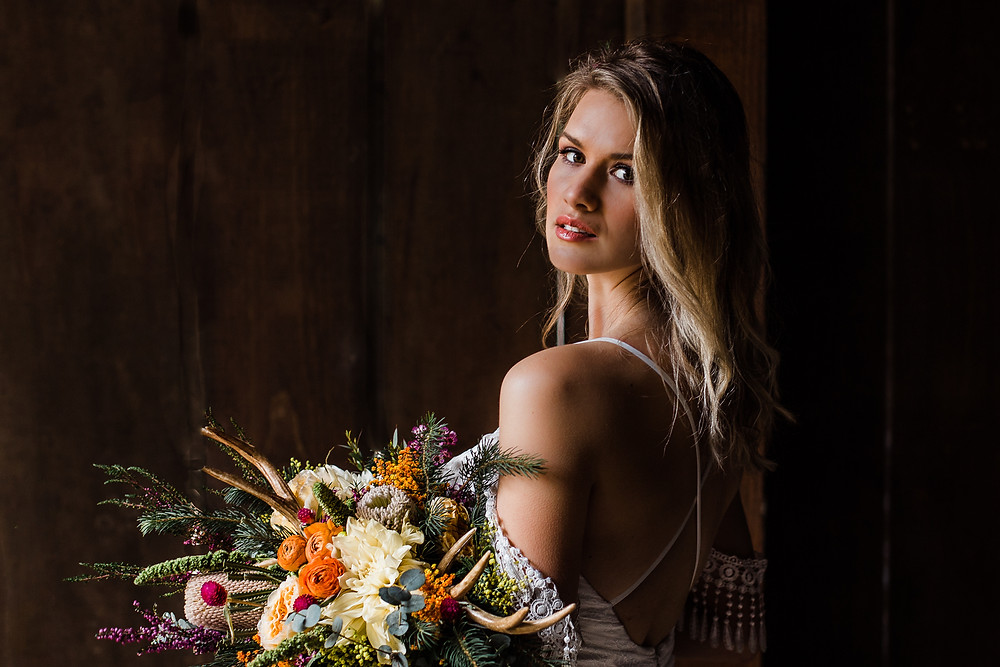 Yosemite boho bride looking over her shoulder while holding a large bouquet with antlers