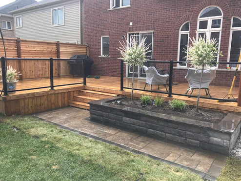 Custom Deck Build with Regal Railing including Glass. Retaining Wall for Garden and Interlock Design