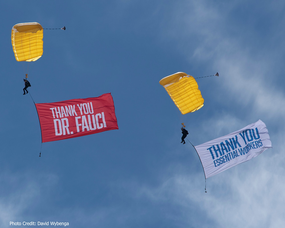 Two yellow parachutes with giant thank you flags