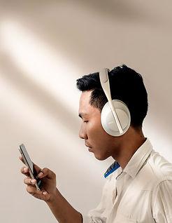 Man listening to podcast on phone through white headphones