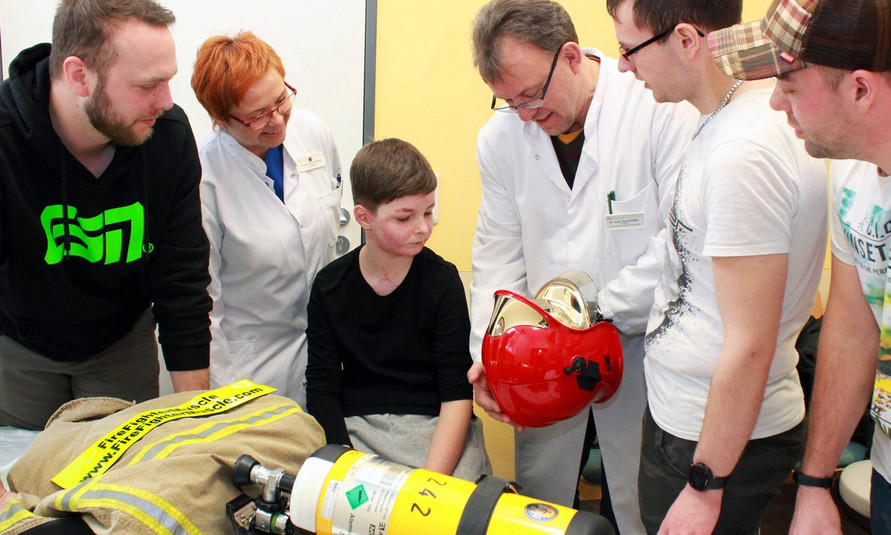 csm_Feuerwehrmaenner_im_Gespraech_mit_brandverletzten_Kindern_e839334743.jpg