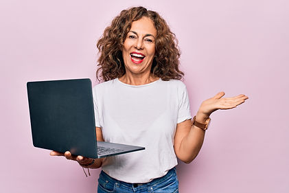 Middle age beautiful business woman working using laptop over isolated pink background cel...r e.jpg