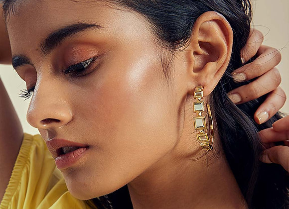 The metal pyramid hoop earrings of ISHARYA worn.