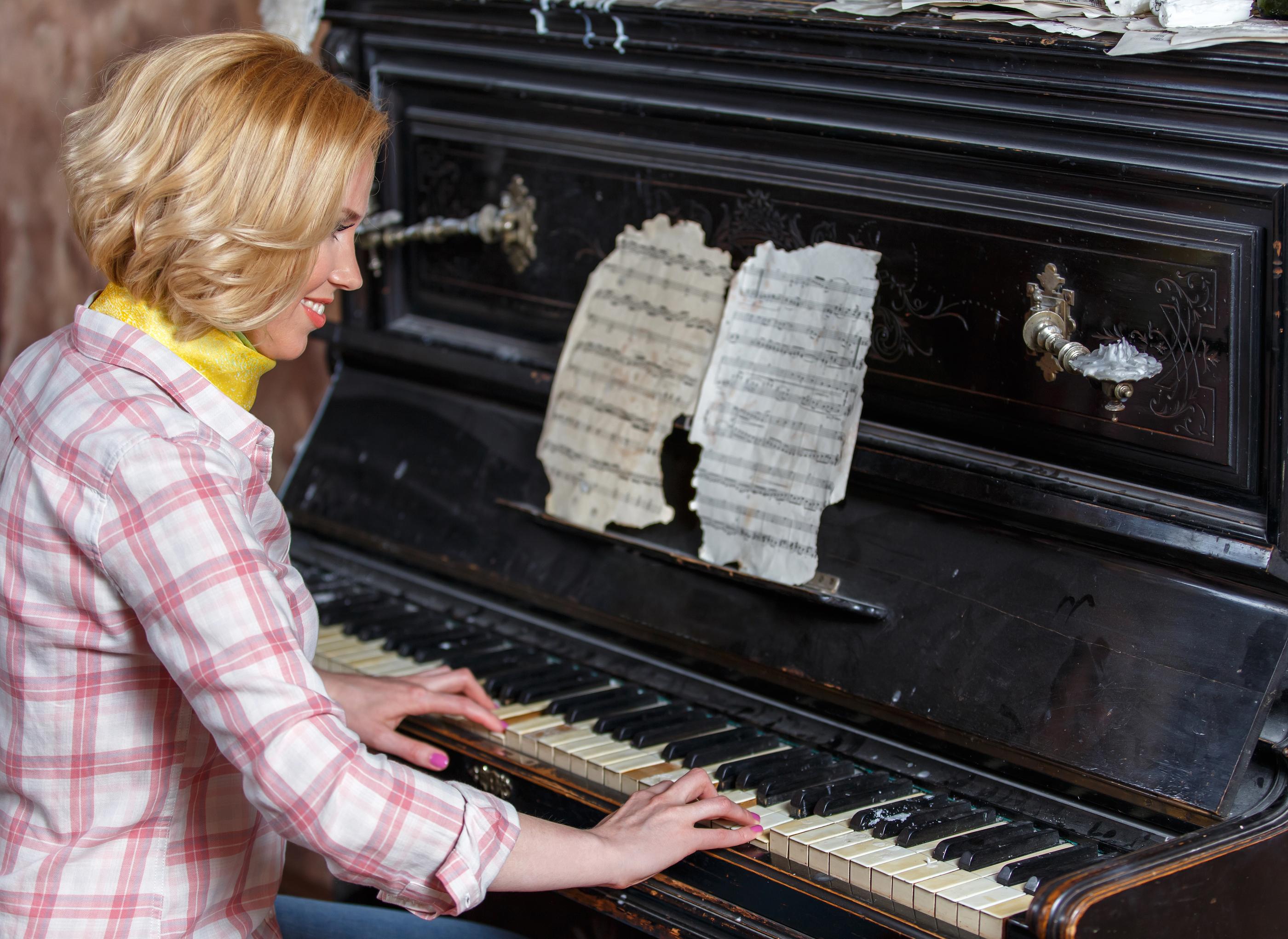 Smiling Female Musician Playing Sheet Music On Retro Piano