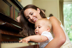 Mother Smiling As Baby Plays Piano