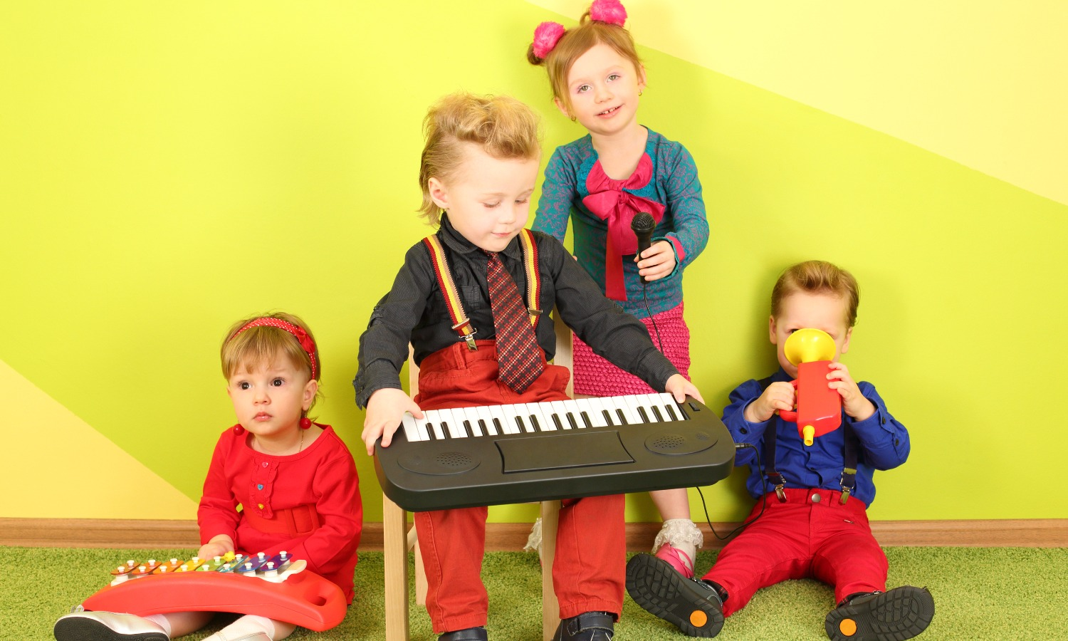 Four children with microphone and musical instruments_ toy piano, metallophone and toy trumpet_edite