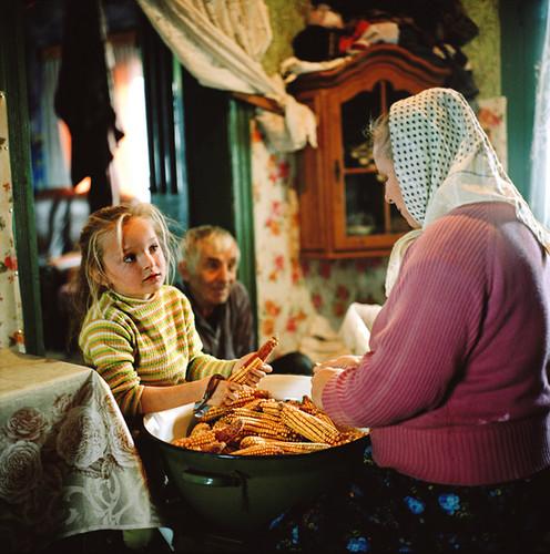 艾恩·佩特里克和他的妻子玛丽亚·弗拉加在教他们的邻居七岁的阿德里亚娜·唐塔斯剥玉米做牛饲料。罗马尼亚马拉穆列什。   雷娜·阿芬第   2012
