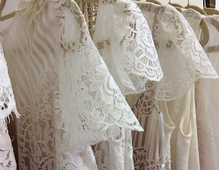 A row of modern, lace wedding dresses. Sleeves mostly in view.