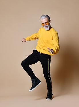 Happy senior millionaire man dancing in