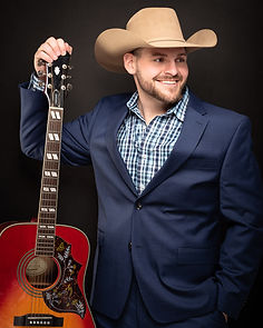 Picture of a man in a blue suit wearing a cowboy hat and holding his guitar.