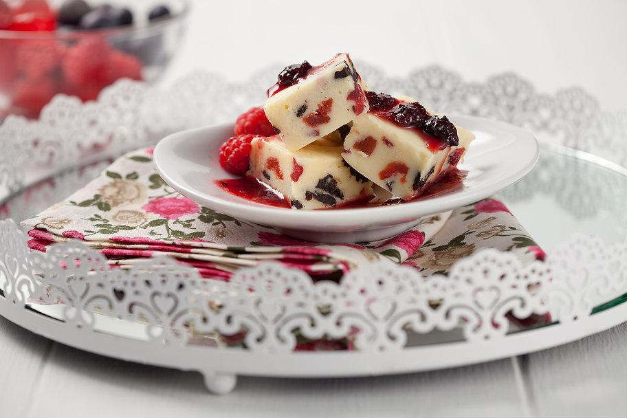 Fudges de frutas vermelhas numa bandeja branca com guardanapo florido