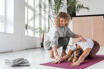 full-shot-teacher-helping-woman-yoga_23-