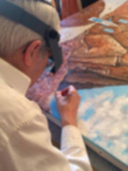 "Artist Stephen Shoel Wachtel, using magnifier lenses, adds fine detail to ""Moses at Sinai,"" a prophetic image of the walled city of Jerusalem."
