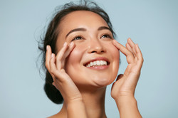 Skin care. Woman with beauty face touching healthy facial skin portrait. Beautiful smiling