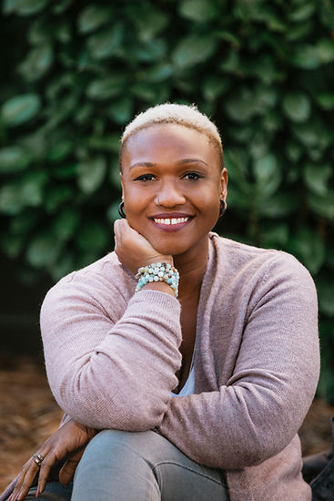 Picture of middle aged Black woman smiling with short ash blond hair in nature