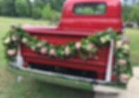 Floral garland on antique red truck