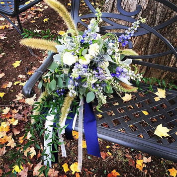 large bohemian bouquet of blue delphinium, blue thistle and white roses with trailing greens