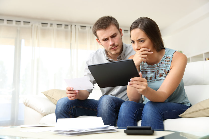 Worried couple checking bank account trouble online in a tablet sitting on a couch in the