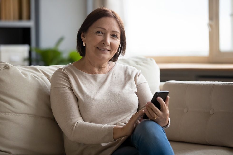 Portrait of smiling middle aged lady resting on sofa, using cellphone. Happy senior old wo