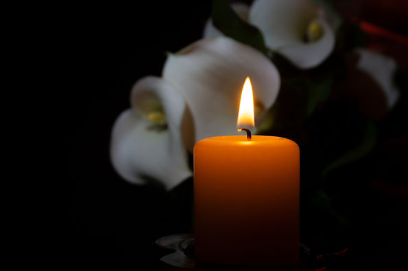 A close up of an orange candle and flame and lily flowers on a dark background._edited.jpg