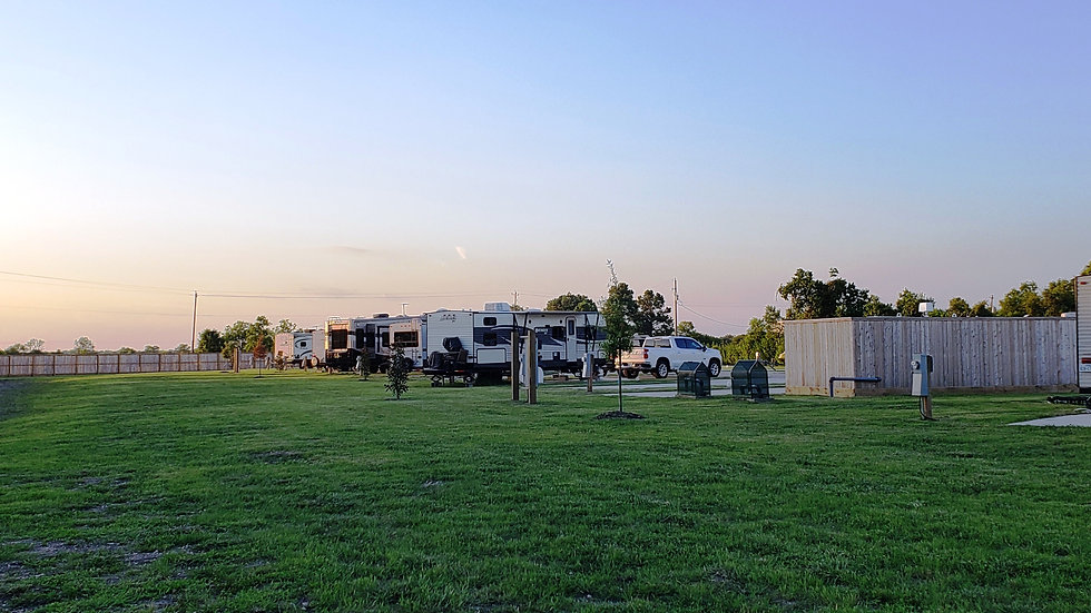 Photo of RV large RV sites with green grassy area behind the concrete parking pads