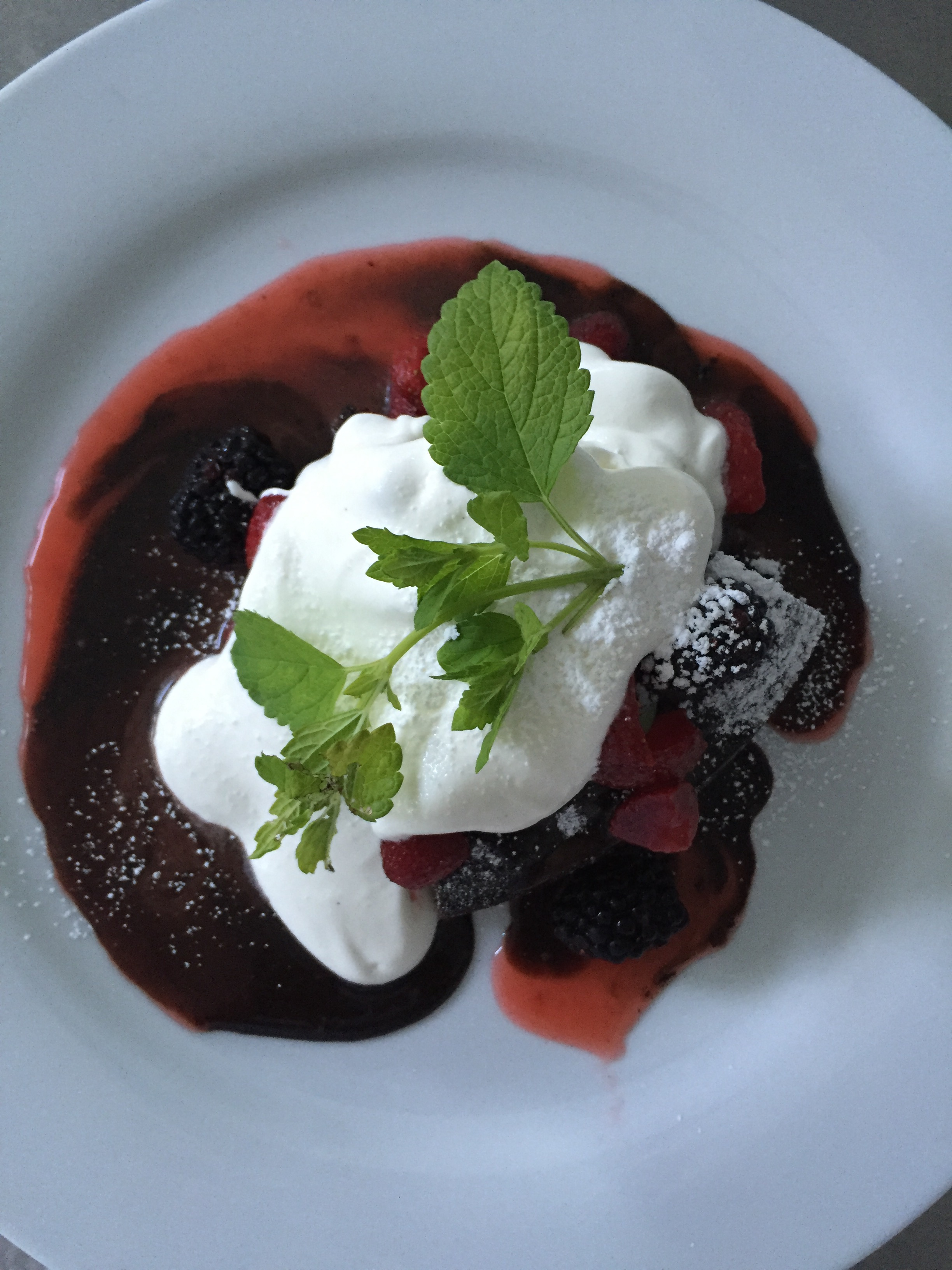 flourless chocolate cake served with a berry reduction, fresh berries whipped cream