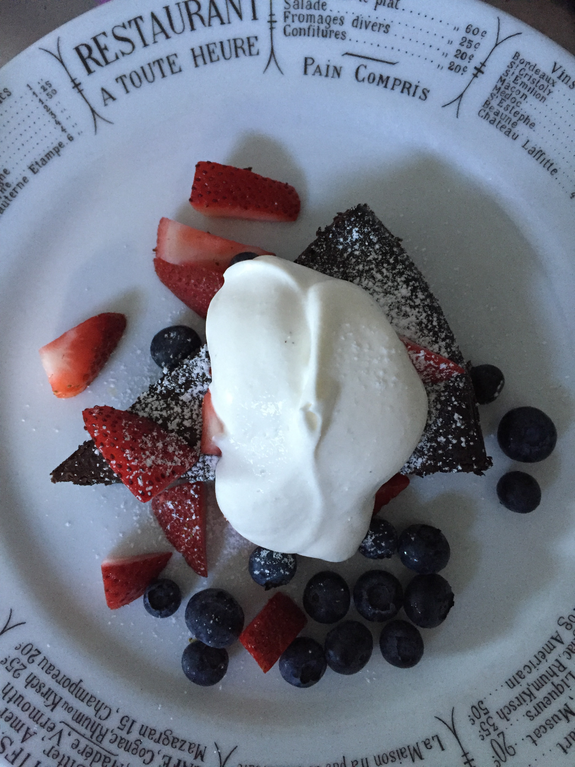 flourless chocolate cake served with whipped cream and fresh berries