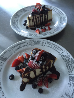 cheese cake with decadent chocolate drizzle and fresh berries