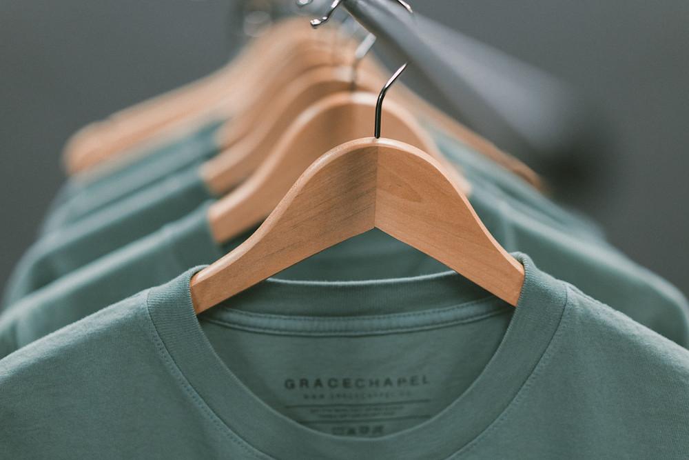 designer green t shirts hanging on rail