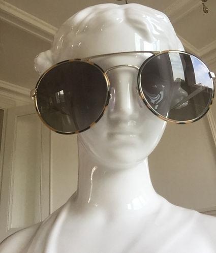 prada sunglasses on a white statue