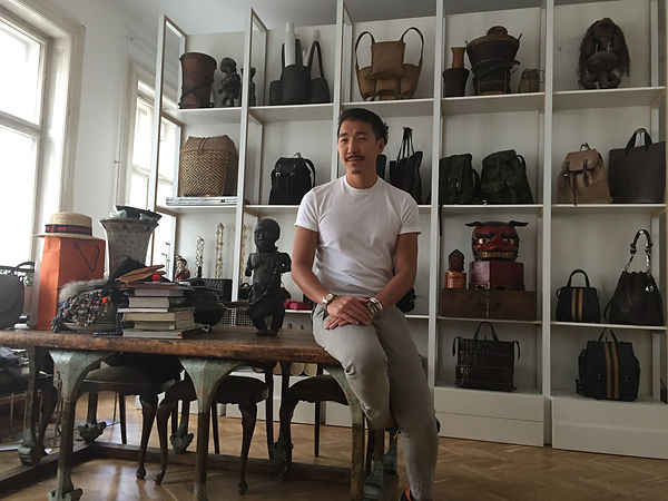 Fashion designer Anh Tuan in his showroom sitting on a table in front of a shelter full of bags